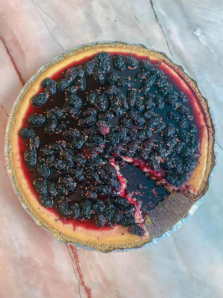 mulberry cheesecake with a slice taken out