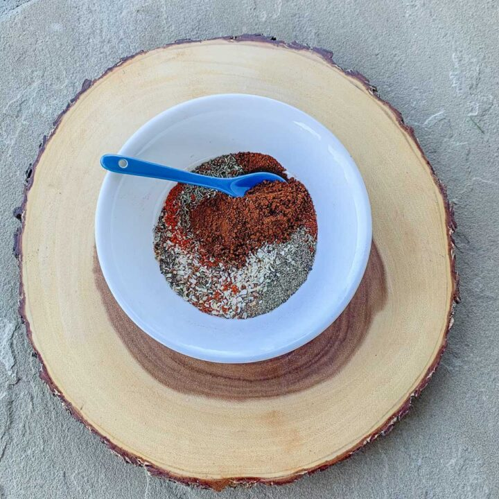 coffee rub ingredients in a white bowl over s wooden slab