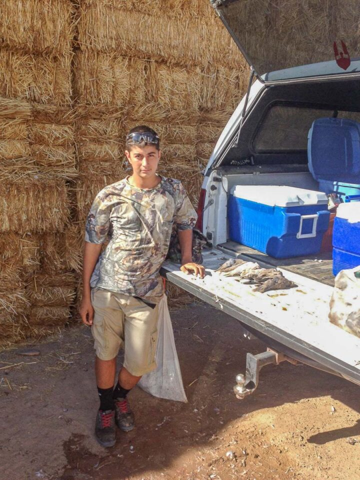 young hunter behind a truck with tail down and dove lining the back