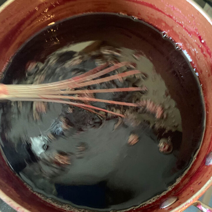 chokecherry syrup being whisked in a pot