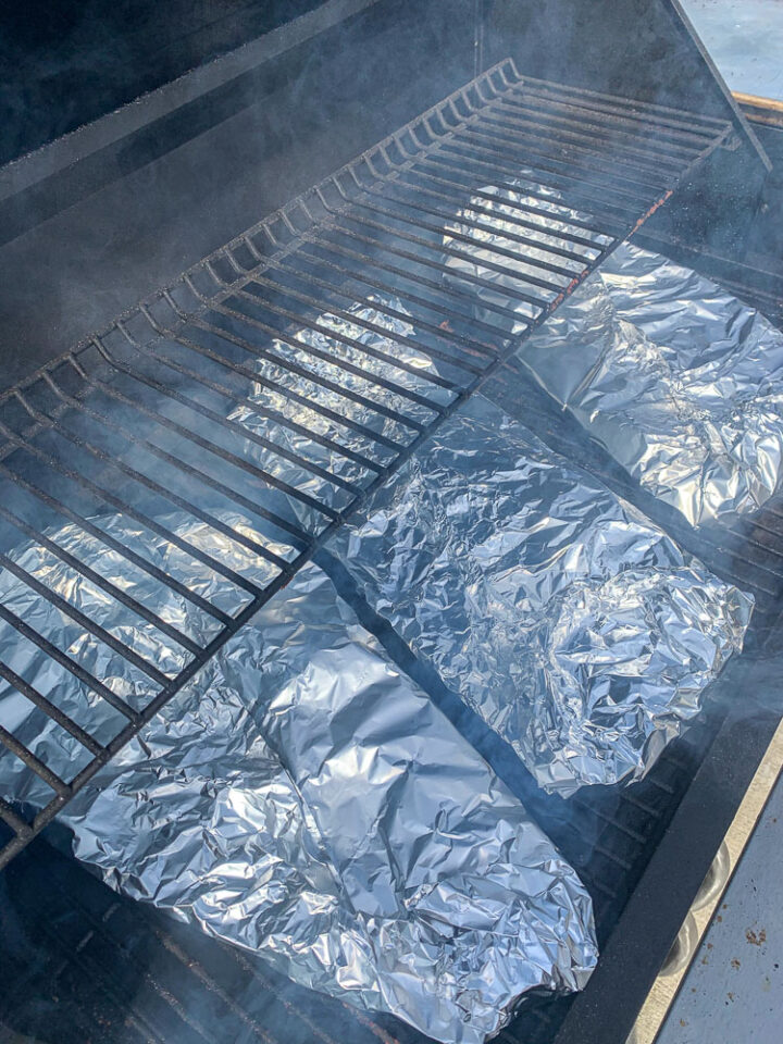 3 foil-wrapped racks of ribs being smoked